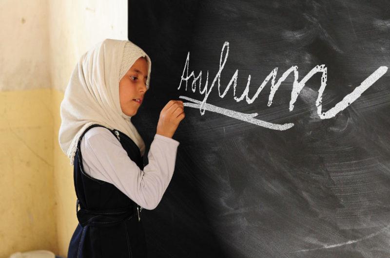 Girl Writing Asylum on Black Board